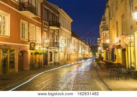 Vilnius, Lithuania - July 8, 2016: View Of Deserted Pilies Street Of Old Town In Bright Evening Illumination With White Motion Blur Effect On Cobbled Road, Famous Landmark Under Summer Night Blue Sky.