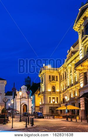 Vilnius, Lithuania. Side View Of Lithuanian National Philharmonic Society Building In Bright Evening Illumination On Ausros Vartu Street In Summer Under Blue Sky