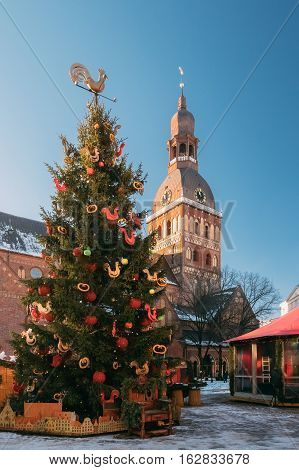 Christmas Market On The Dome Square With Riga Dome Cathedral In Riga, Latvia. Christmas Tree And Trading Houses With Sale Of Christmas Gifts, Sweets And Mulled Wine. Famous Landmark.