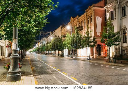 Vilnius, Lithuania. The Night View Of Deserted Gediminas Avenue With Growing Green Trees And Old Illuminated Architecture Under Summer Dark Blue Sky.