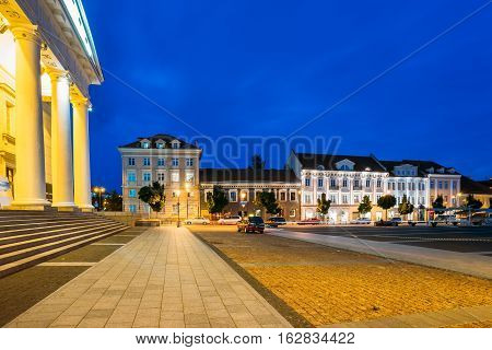 Vilnius, Lithuania. The Evening View Of Didzioji Street With Old Architecture And The Columns Of City Council Administrative Building In Bright Illumination Under Summer Evening Blue Sky.