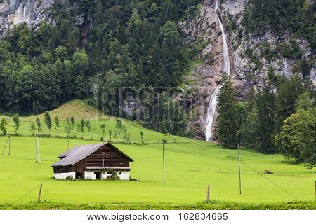 Alpine mountain landscape - small house on a green meadow against the background of a waterfall. Switzerland. Canton Glarus