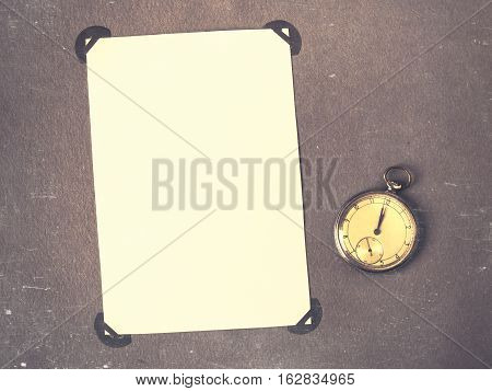Old photo album page with photos and pocket watches