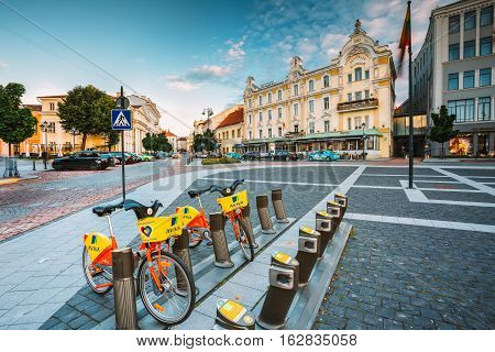 Vilnius, Lithuania  - July 8, 2016: Two Colorful Bicycles For Rent At The Municipal Bike Parking On Didzioji Street, The Ancient Showplace In Old Town. Radisson Blu Royal Astorija Hotel Behind In Summer, Blue Sky