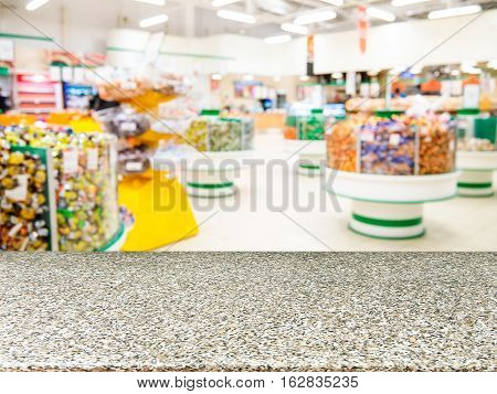 Marble board empty table in front of of supermarket shelves. Mock up for display or montage products