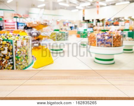 Wooden board empty table in front of of supermarket shelves. Perspective light wood over blur in supermarket. Mock up for display or montage products
