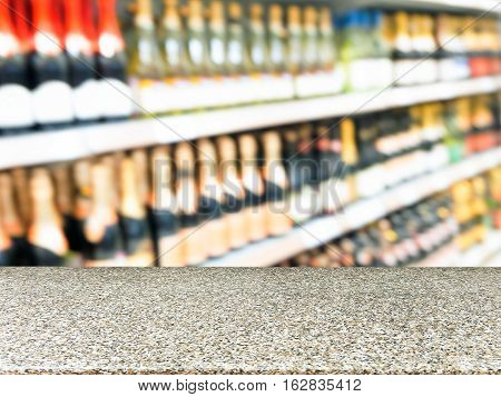Marble board empty table in front of blurred background. Blurred alcohol bottles on shelves in supermarket. Mock up for display of product.