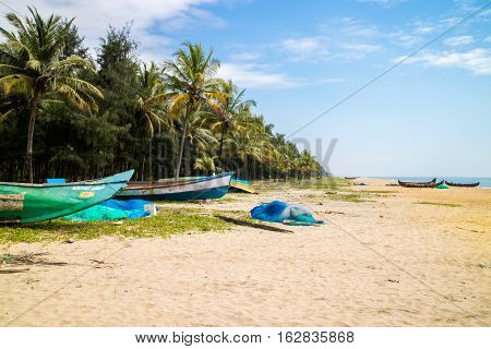 Abandonned artistic wooden canoe on a lonely beach in India Kerala
