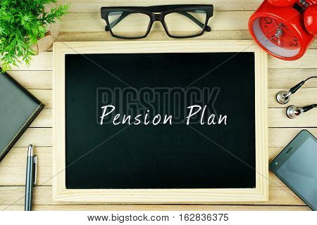 Top view of earphone, calculator, alarm clock, spectacle, notebook, pen, smartphone and chalkboard written with PENSION PLAN.