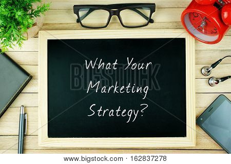 Top view of earphone, calculator, alarm clock, spectacle, notebook, pen, smartphone and chalkboard written with WHAT YOUR MARKETING STRATEGY.