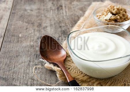 Greek yogurt in glass bowl on wooden table
