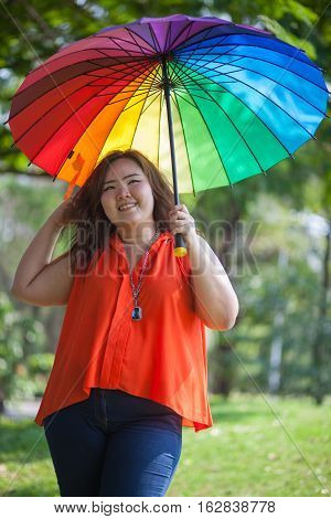 Happy fatty asian woman with umbrella outdoor in a park