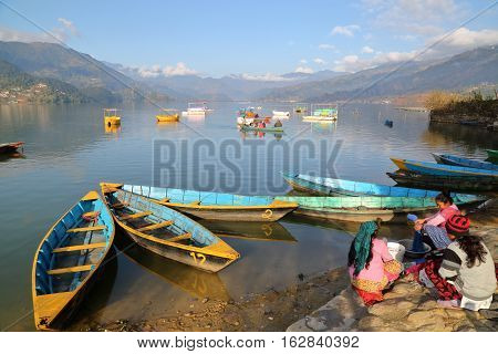 POKHARA, NEPAL - JANUARY 5, 2015: Nepalese women washing clothes along the shore of Phewa Lake, Pokhara, Nepal