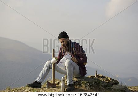 young handsome bearded hipster man in checkered shirt with long beard holding axe or ax on mountain top on natural background with sky
