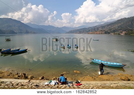 POKHARA, NEPAL - JANUARY 8, 2015: Nepalese woman washing clothes along the shore of Phewa Lake