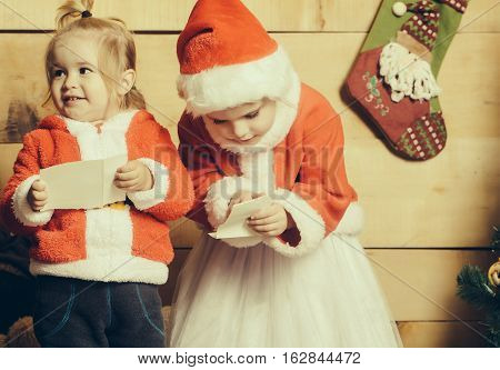 christmas children in red santa claus hat and coat reading from paper sheet at xmas decoration sock. cute kids boy and girl at new year holidays celebration
