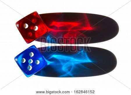 Two tiny translucent plastic dice with long shadows. Red and blue dice in sunlight with shiny colorful shadow cones. Light reflects in transparent material and shows exciting effects. Macro photo.