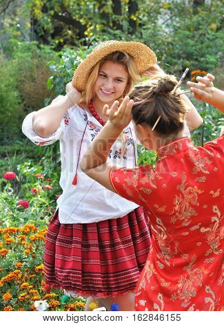 two teenage girls in traditional ukrainian and chinese clothes in the summer landscape