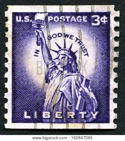 UNITED STATES OF AMERICA - CIRCA 1954: A used US postage stamp depicting an illustration of the Statue of Liberty and the quote In God We Trust circa 1954.