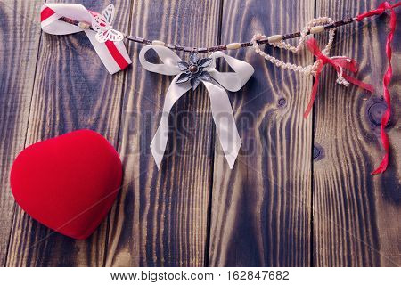 white bow and different ribbons hanging on a rope and red heart on a wooden background