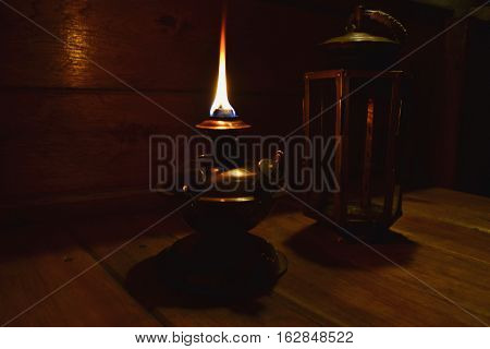 a copper kerosene lamp burns on a table in a night-time