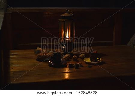 an age-old lamp is conflagrant on a table alongside steklyanaya vase and cups