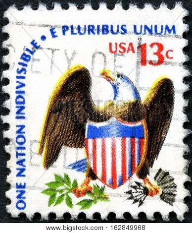 UNITED STATES OF AMERICA - CIRCA 1975: A used postage stamp from the USA depicting the American Eagle and flag and a line from the pledge of Allegiance circa 1975.