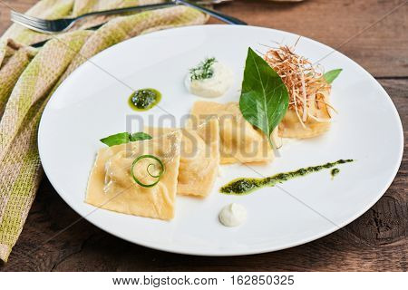 Ravioli with duck and cream sauce, served on a white plate