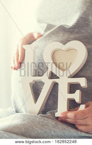 Young pregnant woman holds wooden letters LOVE. Love and maternity concept.