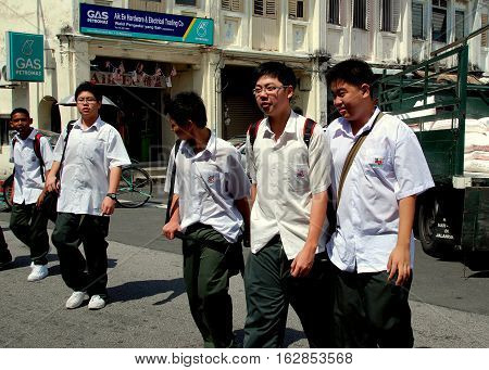 Georgetown Malaysia - January 8 2008: A group of Malaysian schoolboys wearing uniforms of green-gray trousers and short-sleeved white shirts walking on Lebuh Kimberley