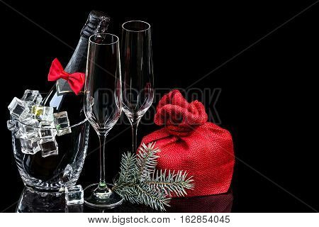 Bottle of champagne in an ice bucket with wineglasses and gift in bag