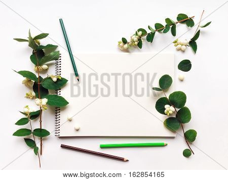 Natural composition with sketchbook and pencils on white background decorated with green snowberry branches and berries. Flat lay top view view from above