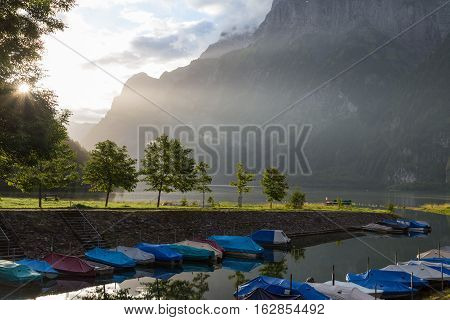 Foggy morning in Swiss Alps. Lake on the background of mountain peaks lit sun. Boat dock.