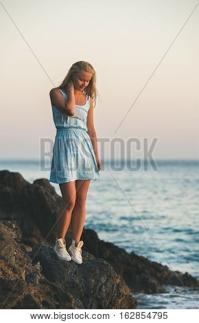 Young blond tourist woman in blue dress standing on natural rocks by the sea at sunset and looking down. Kleopatra beach, Alanya, Mediterranean region, Turkey