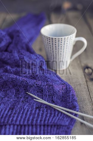 Beautiful blue knitted sweater needles and cup of hot tea on wooden table. Cozy winter. Hobbies. Selective focus.