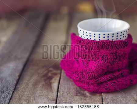 Cup of hot tea wrapped in knitted scarf on old wooden table. Winter cozy mood. Copyspace. Selective focus