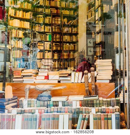 Paris France - October 17 2016: unidentified man is sitting in an antiquarian book shop in Paris. Paris is the capital of France and one of Europes major financial cultural and commercial centres