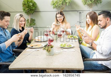 Friends Taking Photos Of Their Food