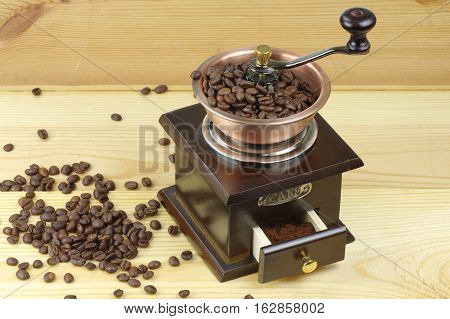 Old-style manual coffee grinder on a rustic table with wooden planks. Around the mill are scattered coffee beans.