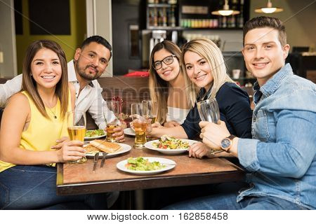 Five Friends Eating In A Restaurant