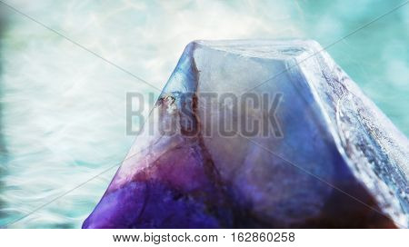 Beautiful triangular piece of multicolored glycerin soap against a wavy glass table top.