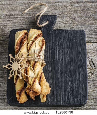 Black slate cutting board for records with cozy flavored cookies with cinnamon. The concept of comfort food. Top view. Style hygge