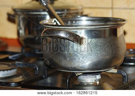 Two steel pots stand on a gas cooker. On one of them you can see the dew. Closeup image.