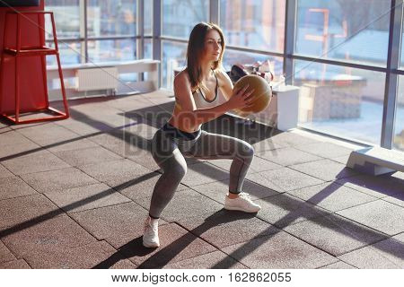 Young Woman Doing Squats With Medicine Ball In Gym