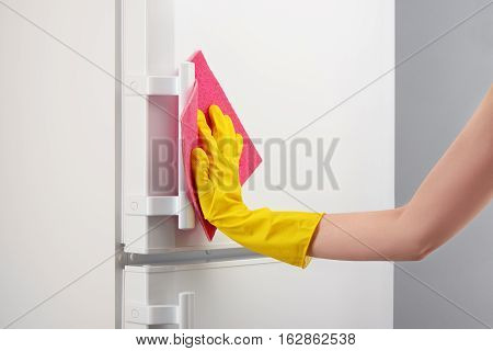 Hand In Yellow Glove Cleaning White Refrigerator With Pink Rag