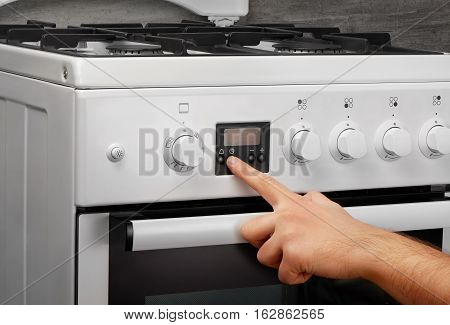 Male Hand Turning On White Kitchen Gas Stove On Gray