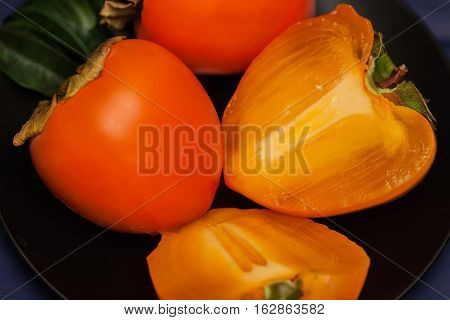 Cut a ripe persimmon in black plate, low key. Sweet, delicious flesh of Persimmon is packed with vitamins, minerals, antioxidants vital for optimum health