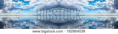 Spectacular blue and white panoramic cloudscape with clear water reflections. Photograph was shot at sea from the deck of a boat looking toward land.