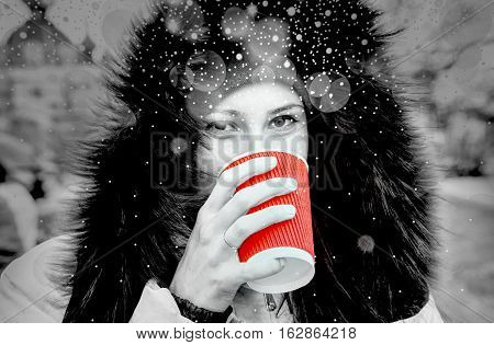 Yound girl drinks a red cup of hot tea black and white filtered with shiny snowfall with dramatic light