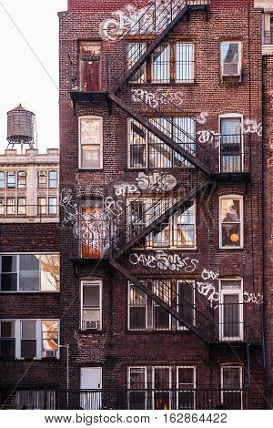 Back side of a brick apartment building in Manhattan, showing the fire escape and graffiti on its facade.